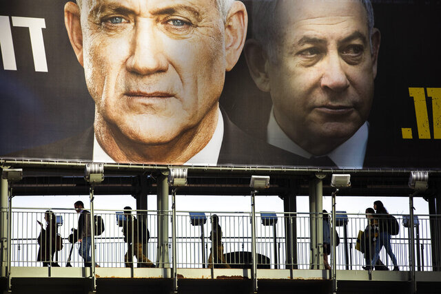 FILE - In this Feb. 18, 2020 file photo, people walk on a bridge under an election campaign billboard for the Blue and White party, then an opposition party led by Benny Gantz, left, and showing Israeli Prime Minister Benjamin Netanyahu, in Ramat Gan, Israel. After three deadlocked and divisive elections, and a year and a half of political paralysis, Israel is finally swearing in a new government, with Netanyahu securing a historic fifth term in office thanks to a controversial power-sharing deal with rival-turned-partner Gantz. The deal calls for Netanyahu to serve as prime minister for the government's first 18 months before being replaced by Gantz. (AP Photo/Oded Balilty)