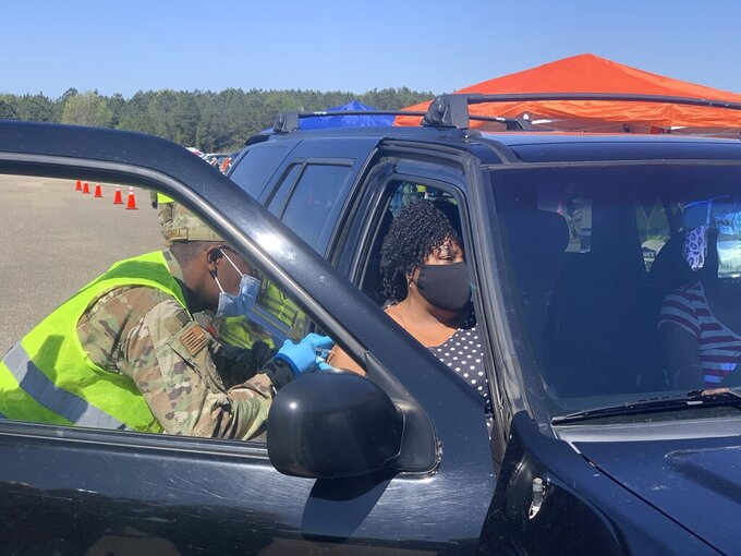 Alabama National Guard Sgt. Antwan Marshall gives a COVID-19 vaccination to Shirley Thompson on Friday, April 2, 2021 during a clinic at Wilcox High School in Camden, Ala. (AP Photo/Kim Chandler)