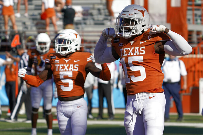 Texas' Chris Brown (15) and D'Shawn Jamison (5) celebrates after a stop against West Virginia on fourth down late during the second half of an NCAA college football game in Austin, Texas, Saturday, Nov. 7, 2020. (AP Photo/Chuck Burton)