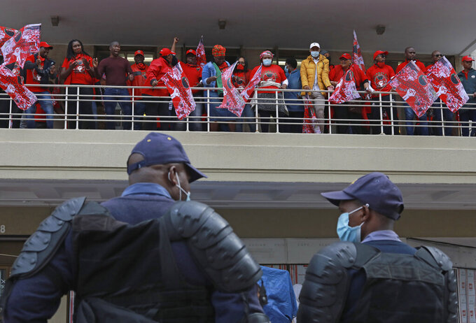 Police keep an eye on protesting members of the National Education, Health and Allied Workers' Union (NEHAWU) in Cape Town, South Africa, Thursday Sept. 3, 2020. NEHAWU are calling for safer working conditions for front line workers after 240 lost their lives to COVID-19. (AP Photo/Nardus Engelbrecht)