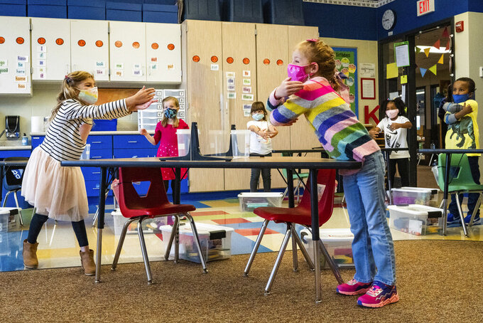 """FILE - In this Sept. 10, 2020, file photo, Kindergarten students practice air hugs while watching a video on how to """"greet from 6 feet"""" during class at Wildwood Elementary in Stillwater, Minn. Students are socially distanced in the classroom and have plexiglass barriers between them and their table mates. (Evan Frost /Minnesota Public Radio via AP, File)"""