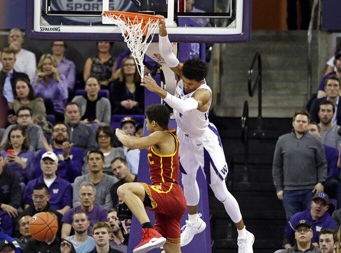 Washington's Matisse Thybulle swings from the basket after dunking over Southern California's Derryck Thornton during the first half of an NCAA college basketball game Wednesday, Jan. 30, 2019, in Seattle. (AP Photo/Elaine Thompson)
