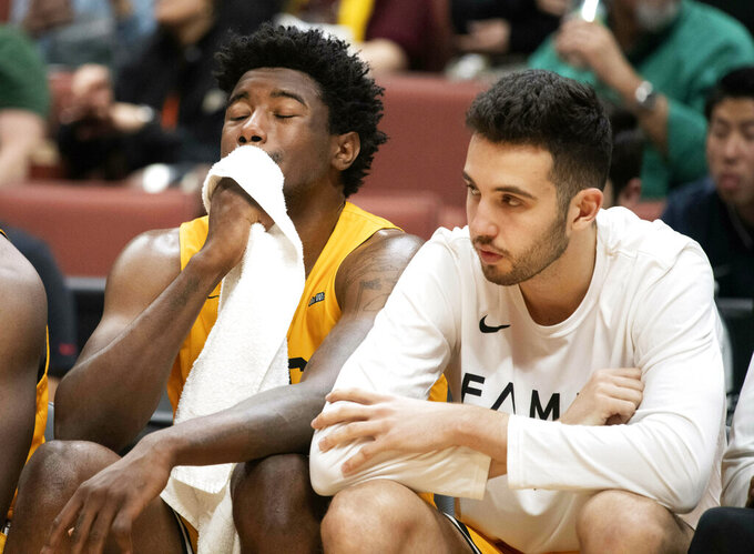 Long Beach State forward Mason Riggins, left, wipes his face with a towel as the team plays the final minutes of an NCAA college basketball game against UC Irvine at the Big West men's tournament in Anaheim, Calif., Friday, March 15, 2019. UC Irvine won 75-67. (AP Photo/Kyusung Gong)