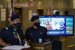 Police wearing face masks to help curb the spread of the coronavirus stand in front of a body temperature measuring machine at a building in Kuala Lumpur, Malaysia, Monday, Oct. 26, 2020. Senior Minister Ismail Sabri Yaakob announce conditional movement control order (MCO) in Kuala Lumpur, Selangor and Putrajaya will be extended for another two weeks until Nov 9. (AP Photo/Vincent Thian)