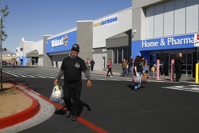 Eddie Medina, 62, carries groceries he bought for his wife at the reopening of the Cielo Vista Walmart, Thursday, Nov. 14, 2019, in El Paso, Texas. He said his wife Cecy Medina is a Walmart employee who witnessed the shooting there on Aug. 3 that left 22 people dead. He said she's still too traumatized to enter the store, and is currently in therapy paid for by Walmart. The Texas-shaped logo on his shirt read