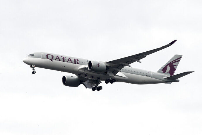 FILE - In this Nov. 7, 2019 file photo, a Qatar Airways jet approaches Philadelphia International Airport in Philadelphia. Long-haul carrier Qatar Airways said Wednesday, July 22, 2020, it launched international arbitration seeking at least $5 billion from four boycotting Arab countries for blocking its flights from their airspace and their markets, years into a simmering political dispute between the nations. (AP Photo/Matt Rourke, File)