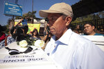Fernando Bonilla Realegeno carries a small coffin holding the bones of his father Jose Bonilla, who was killed when Fernando was in his early 20s, as relatives receive the remains of six family members who were killed in a 1982 massacre in San Salvador, El Salvador, Thursday, Jan. 23, 2020. The remains of six adults and children from one family were handed over to surviving relatives Thursday, 38 years after the El Calabozo massacre, in which government soldiers are accused of killing more than 200 people. (AP Photo/Salvador Melendez)