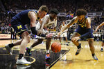 Michigan center Jon Teske (15), forward Isaiah Livers (2) and Purdue forward Trevion Williams (50) go for a loose ball during the second half of an NCAA college basketball game in West Lafayette, Ind., Saturday, Feb. 22, 2020. (AP Photo/Michael Conroy)