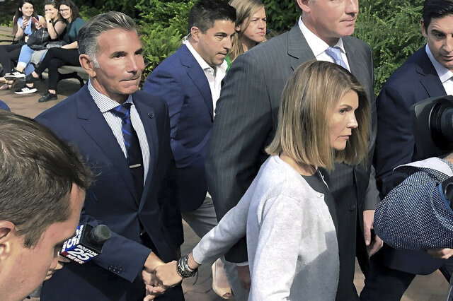 FILE - In this Aug. 27, 2019, file photo, Lori Loughlin departs federal court in Boston with her husband, Mossimo Giannulli, left, after a hearing in a nationwide college admissions bribery scandal. In August 2020, the couple was sentenced to prison after pleading guilty for paying bribes to get their two daughters into the University of Southern California as rowing recruits. (AP Photo/Philip Marcelo, File)