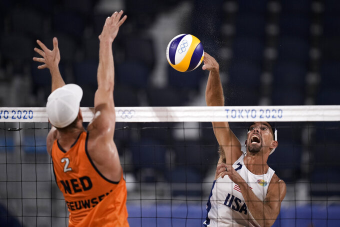 Robert Meeuwsen, of the Netherlands, blocks against Nicholas Lucena, of the United States, during a men's beach volleyball match at the 2020 Summer Olympics, Saturday, July 24, 2021, in Tokyo, Japan. (AP Photo/Felipe Dana)