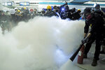 Demonstrators spray fire extinguishers during a protest at the Yuen Long MTR station in Hong Kong, Wednesday, Aug. 21, 2019. Hong Kong riot police faced off briefly with protesters occupying a suburban train station Wednesday evening following a commemoration of a violent attack there by masked assailants on supporters of the anti-government movement. (AP Photo/Kin Cheung)
