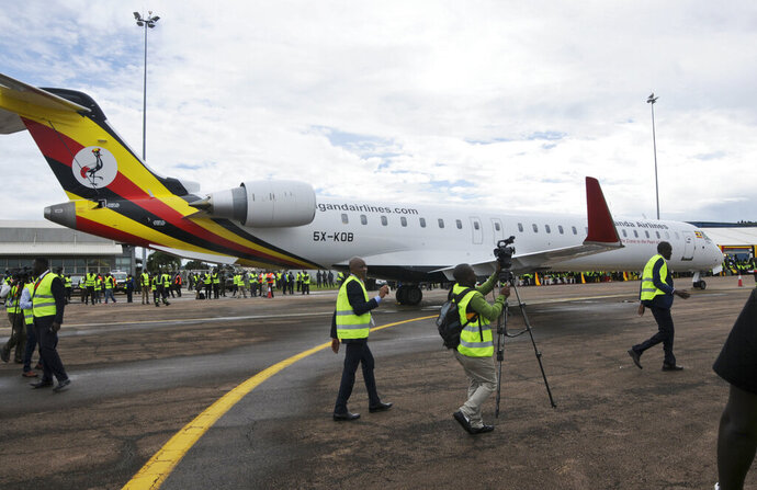 FILE - In this Tuesday, April 23, 2019 file photo, cameramen film at a ceremony to mark the arrival of two CRJ-900 jets from Canadian aerospace company Bombardier, at the airport in Entebbe, Uganda. Uganda's national carrier