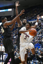 Connecticut's Alterique Gilbert, looks to pass around the defense of Central Florida's Collin Smith, left, and Central Florida's Chad Brown, back, during the first half of an NCAA college basketball game, Saturday, Jan. 5, 2019, in Hartford, Conn. (AP Photo/Jessica Hill)