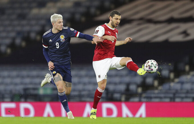 Scotland's Lyndon Dykes, left, and Austria's Aleksander Dragovic their 2022 World Cup qualifying soccer match between Scotland and Austria, at Hampden Park in Glasgow, Scotland, Thursday March 25, 2021. (Jane Barlow/PA via AP)