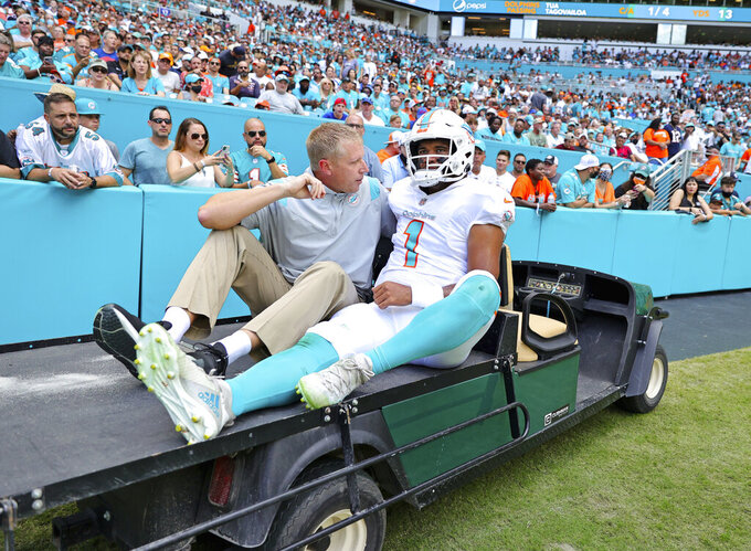 Miami Dolphins quarterback Tua Tagovailoa (1) is assisted off the field during the first half of an NFL football game against the Buffalo Bills, Sunday, Sept. 19, 2021, in Miami Gardens, Fla. (David Santiago,Miami Herald via AP)