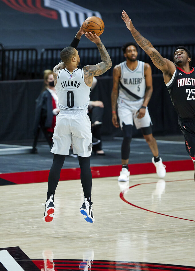 Portland Trail Blazers guard Damian Lillard, left, shoots a 3-point basket over Houston Rockets forward Cameron Oliver during the first half of an NBA basketball game in Portland, Ore., Monday, May 10, 2021. (AP Photo/Craig Mitchelldyer)