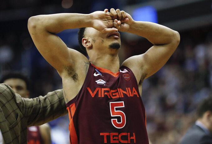 Virginia Tech guard Justin Robinson covers his face after the team's loss to Duke in an NCAA men's college basketball tournament East Region semifinal in Washington, Friday, March 29, 2019. Duke won 75-73. (AP Photo/Patrick Semansky)