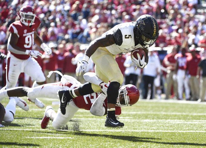 Vanderbilt running back Ke'Shawn Vaughn slips past Arkansas defender Kamren Curl to score a touchdown in the second half of an NCAA college football game Saturday, Oct. 27, 2018, in Fayetteville, Ark. (AP Photo/Michael Woods)