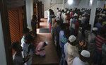 Sri Lankan Muslims offer Friday prayers inside a mosque, in Colombo, Sri Lanka, Friday, April 26, 2019. Across Colombo, there was a visible increase of security as authorities warned of another attack and pursued suspects that could have access to explosives. Authorities had told Muslims to pray at home rather than attend communal Friday prayers that are the most important religious service for the faithful. At one mosque in Colombo where prayers were still held, police armed with Kalashnikov assault rifles stood guard outside. (AP Photo/Manish Swarup)