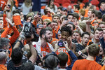 "FILE - In this Feb. 5, 2019, file photo, Illinois forward Giorgi Bezhanishvili, left, and guard Ayo Dosunmu (11) are swarmed by fans after the team's NCAA college basketball game against Michigan State in Champaign, Ill. As the season begins in earnest this week, with a full slate of Division I games Wednesday, fans will notice the absence of traditions such as the Silent Night game across the college basketball landscape. The population of Krzyzewskiville at Duke will be zero, the Oakland Zoo at Pittsburgh a bit more tame. The Orange Crush at Illinois will be less intimidating and the ghost-like sound of ""Rock Chalk Jayhawk"" at Kansas will be merely the echoes from thousands of previous wins.  (AP Photo/Rick Danzl, File)"