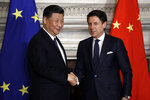 Chinese President Xi Jinping, left, and Italian Premier Giuseppe Conte shake their hands at the end of the signing ceremony of a memorandum of understanding at Rome's Villa Madama, Saturday, March 23, 2019. Italy signed a memorandum of understanding with China on Saturday in support of Beijing's
