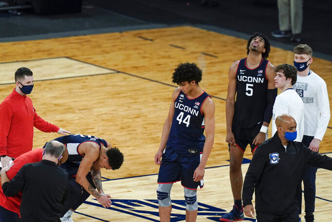 Connecticut's James Bouknight, left, Andre Jackson, center, and Isaiah Whaley, right, react after the team's 59-56 loss to Creighton in an NCAA college basketball game in the semifinals in the Big East men's tournament Friday, March 12, 2021, in New York. (AP Photo/Frank Franklin II)