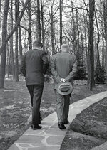 FILE - In this April 22, 1961, file photo, with their heads bowed, President John F. Kennedy, left, walks along a path at Camp David near Thurmont, Md., with former President Dwight D. Eisenhower, as the two met to discuss the Bay of Pigs invasion. Researchers at the John F. Kennedy Presidential Library and Museum in 2020 have found a cache of letters from Americans objecting to JFK's embrace of cocktails at White House events. The letters shed new insight into Eisenhower's handoff to Kennedy early in 1961, and the strikingly different attitudes that people held about alcohol at official functions. (AP Photo/Paul Vathis, File)
