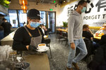 A server wearing a face mask carries a cup of coffee at a Moka Bros cafe in Beijing, Friday, Feb. 14, 2020. For Valentine's Day Moka Bros, a health food eatery in Beijing, offered a special that included both a rose and a note logging the temperature of the chef that made the meal. Like many businesses in China, the restaurant has struggled to cope with the impact of a virus that has infected tens of thousands of people worldwide and sent several cities into lockdown. (AP Photo/Mark Schiefelbein)