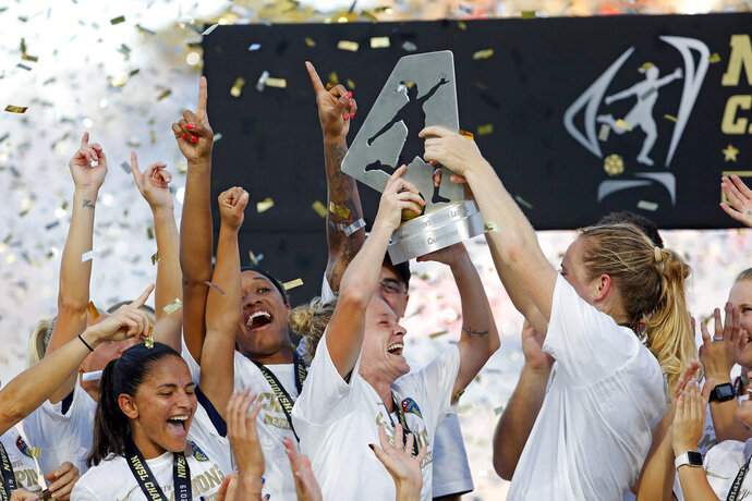 North Carolina Courage's Heather O'Reilly, center, holds the championship trophy following the team's win over the Chicago Red Stars in an NWSL championship soccer game in Cary, N.C., Sunday, Oct. 27, 2019. (AP Photo/Karl B DeBlaker)