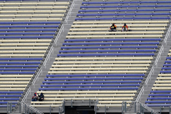 Race fans sit in the stands before a NASCAR Cup Series auto race at Kansas Speedway in Kansas City, Kan., Sunday, Oct. 18, 2020. Up to 10,000 fans will be allowed into the facility. (AP Photo/Orlin Wagner)