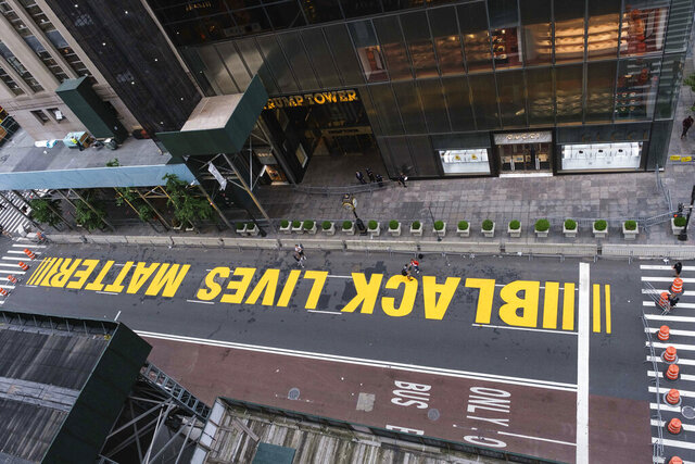 Pedestrians walk on a Black Lives Matter mural painted in front of Trump Tower, Friday, July 10, 2020, in New York. (AP Photo/Yuki Iwamura)