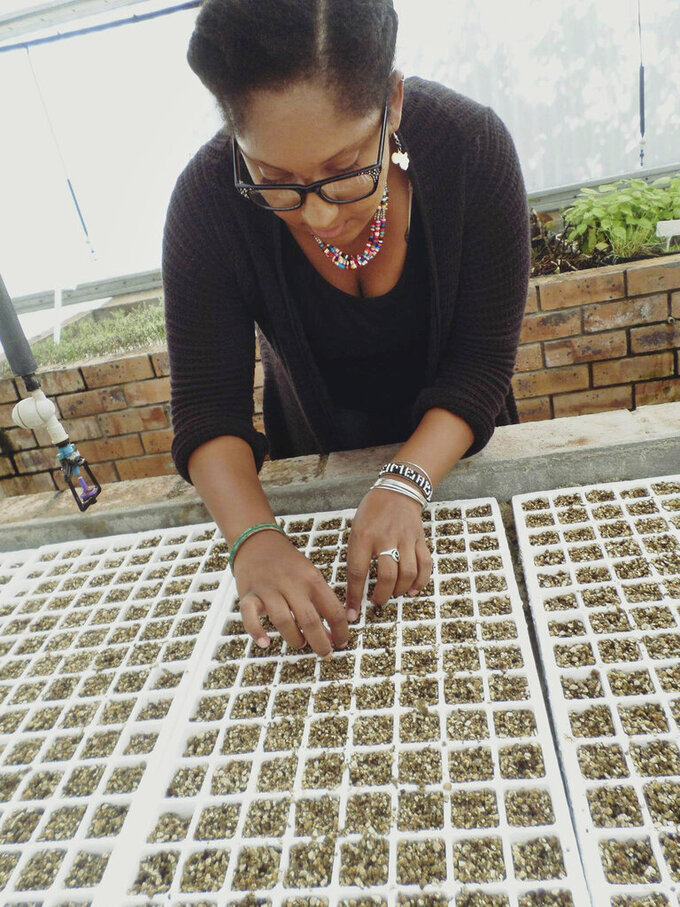 """This 2016 photo provided by Tanisha Williams shows her in Cape Town, South Africa. Williams, a botanist at Bucknell University, knows exactly which plants she's looking for. But after being questioned by strangers in public parks, Williams, who is Black, has started carrying her field guides with her. """"I've been quizzed by random strangers,"""" she said. """"Now I bring my wildflower books and botanical field guides, trying to look like a scientist. It's for other people. I wouldn't otherwise lug these books."""" (Beatrix D. Fields/Tanisha Williams via AP)"""