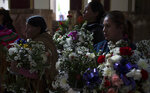 Women hold flower funeral wreaths during a funeral service for Mery Vila, in La Paz, Bolivia, Thursday, July 11, 2019. Vila's partner killed the 26-year-old woman by striking her several times on the head with a hammer. Vila is one of 69 femicides reported in Bolivia since January, the highest in six years in the same period. (AP Photo/Juan Karita)