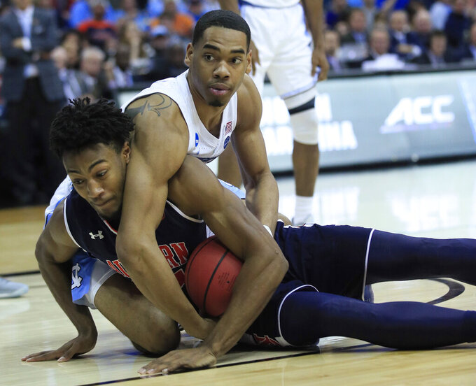 Auburn's Anfernee McLemore, front, and North Carolina's Garrison Brooks dive after a loose ball during the second half of a men's NCAA tournament college basketball Midwest Regional semifinal game Friday, March 29, 2019, in Kansas City, Mo. (AP Photo/Orlin Wagner)