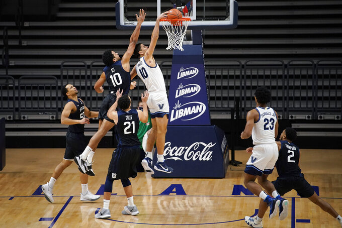 Villanova's Cole Swider, right, goes up for a dunk past Butler's Bryce Nze during the first half of an NCAA college basketball game, Wednesday, Dec. 16, 2020, in Villanova, Pa. (AP Photo/Matt Slocum)