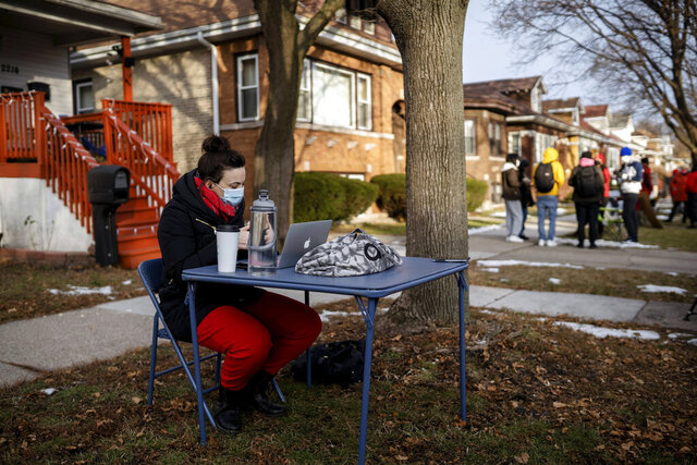Meghan Hayes, who teaches at John Hay Community Academy, teaches her class outside Chicago Public Schools Board President Miguel del Valle's home, Wednesday morning, Jan. 13, 2021, in Chicago. Educators who were teaching remotely joined some teachers who were locked out of their remote teaching accounts because of their refusal to teach in-person due to COVID-19 safety concerns. (Pat Nabong/Chicago Sun-Times via AP)