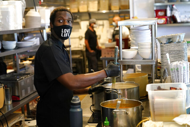 Kinoy Miller prepares food at the Love Life Cafe Thursday, Oct. 29, 2020, in the Wynwood neighborhood of Miami. Florida voters decide Tuesday whether to raise the state's minimum wage to $15 an hour over six years, which advocates say will benefit hundreds of thousands of workers in the Sunshine State's service-heavy economy but which opponents say will stifle industry growth. (AP Photo/Lynne Sladky)