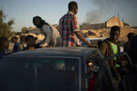 Migrants from Niger jump atop a pickup after being offered a job in the outskirts of Tripoli, Libya, Thursday, Feb. 27, 2020. (AP Photo/Felipe Dana)