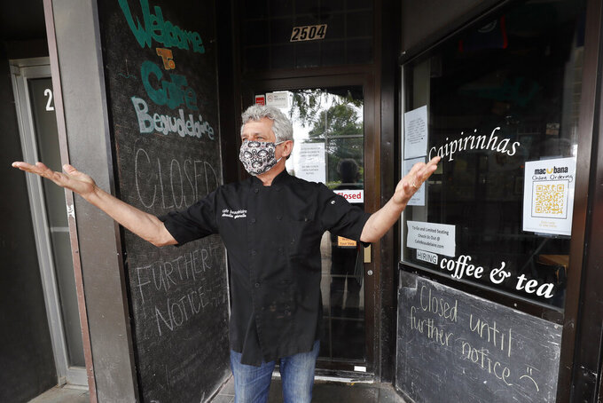 Owner Claudio Gianello stands in the doorway of his temporarily closed Café Beaudelaire restaurant, Tuesday, June 23, 2020, in Ames, Iowa. Within a few weeks of Gov. Kim Reynolds opening bars and restaurants to customers again two major college cities in Iowa are seeing spikes in coronavirus cases among young adults between 19 and 25. In Ames the surge is serious enough to prompt several owners of restaurants and bars near the Iowa State University campus to close voluntarily just weeks after reopening. (AP Photo/Charlie Neibergall)