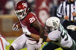 Oklahoma running back Rhamondre Stevenson (29) is tackled by Baylor linebacker Michael McNair (58) during the second half of an NCAA college football game Saturday, Dec. 5, 2020, in Norman, Okla. (AP Photo/Sue Ogrocki)