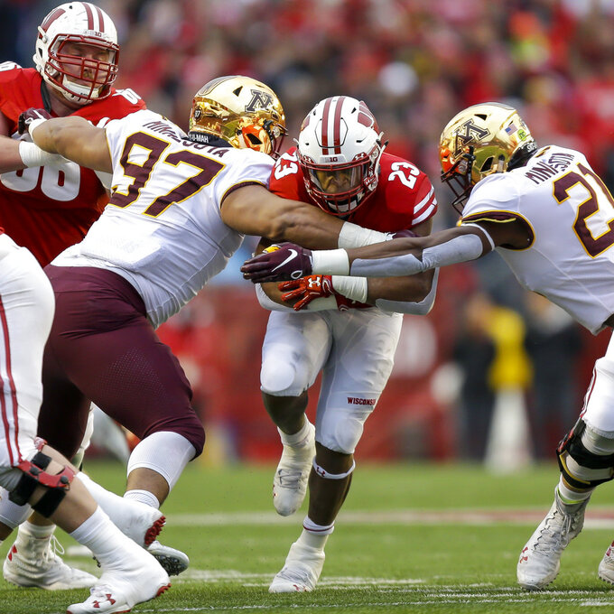 File-This Nov. 24, 2018, file photo shows Wisconsin running back Jonathan Taylor (23) running against Minnesota defensive lineman Royal Silver (97) and linebacker Kamal Martin (21) during the first half of an NCAA college football game in Madison, Wis. Taylor ran for 130 yards on 26 carries for the Badgers in the Orange Bowl. Taylor finished the year with an FBS-freshman-record 1,977 yards. He followed with a fantastic sophomore season and had 1,989 yards rushing (165.8 yards per game) and had four 200-yard games.  (AP Photo/Andy Manis, File)