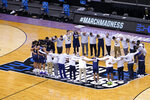Oral Roberts players and coaches huddle on the court after a college basketball game against Florida in the second round of the NCAA tournament at Indiana Farmers Coliseum, Sunday, March 21, 2021 in Indianapolis. Oral Roberts won 81-78. (AP Photo/AJ Mast)