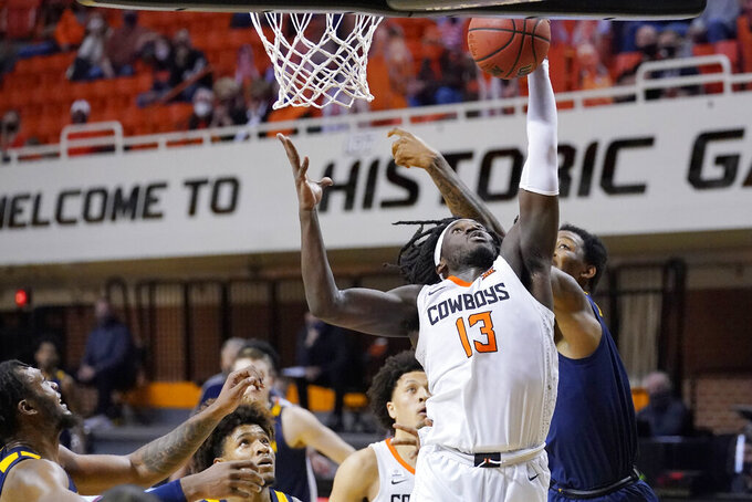Oklahoma State guard Isaac Likekele (13) reaches for a rebound in the second half of an NCAA college basketball game against West Virginia, Monday, Jan. 4, 2021, in Stillwater, Okla. (AP Photo/Sue Ogrocki)