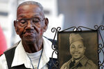 FILE - In this Sept. 12, 2019 file photo, World War II veteran Lawrence Brooks holds a photo of him taken in 1943, as he celebrates his 110th birthday at the National World War II Museum in New Orleans.  Brooks celebrated his 112th birthday, Sunday, Sept. 12, 2021 with a drive-by party at his New Orleans home hosted by the National War War II Museum.   Drafted in 1940, Brooks was a private in the Army's mostly Black 91st Engineer Battalion.   (AP Photo/Gerald Herbert, File)