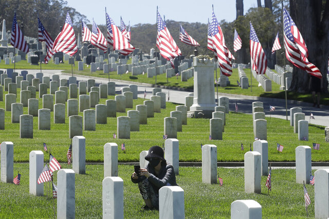 Nancy Graham wears a face mask as she takes photos of a gravestone during the coronavirus outbreak at San Francisco National Cemetery in the Presidio the day before Memorial Day in San Francisco, Sunday, May 24, 2020. (AP Photo/Jeff Chiu)