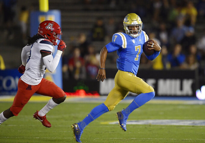 UCLA quarterback Dorian Thompson-Robinson, right, runs the ball as Arizona safety Jarrius Wallace gives chase during the first half of an NCAA college football game, Saturday, Oct. 20, 2018, in Pasadena, Calif. (AP Photo/Mark J. Terrill)