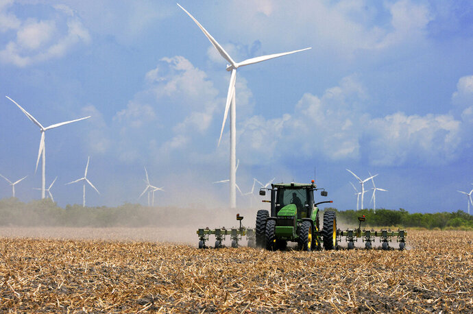 FILE - In this Aug. 17, 2015, file photo, a farmer plows his recently harvested field under wind turbines in the agricultural area north of Rio Hondo, Texas, near the New Mexico border. A California-based renewable energy developer plans to increase by seven-fold its investments as it prepares to build more wind farms in the heart of New Mexico over the next several years. An analysis commissioned by Pattern Development shows a $1.2 billion economic impact from its wind farms in eastern New Mexico and West Texas, surpassing initial projections. (Jason Hoekema/Valley Morning Star via AP, File)