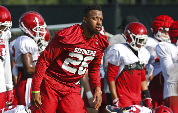 Oklahoma running back Kennedy Brooks warms up with teammates during an NCAA college football practice in Norman, Okla., Monday, Aug. 5, 2019. (AP Photo/Sue Ogrocki)