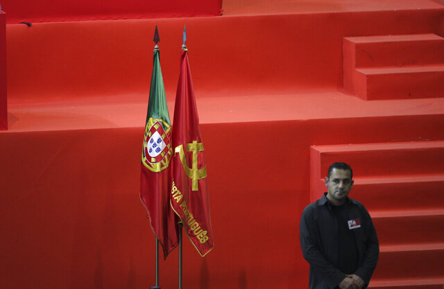 FILE - In this Dec. 4, 2016, file photo, a party member stands next to the flags of Portugal, left, and of the Portuguese Communist Party, near the stage, during the party congress in Almada, south of Lisbon. Health authorities in Portugal are allowing the country's Communist Party to let 16,500 people into its annual open-air festival next weekend. The festival features concerts and political speeches in a fenced-off area of countryside south of Lisbon. (AP Photo/Armando Franca)