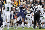 Navy quarterback Malcolm Perry (10) is tackled by South Florida linebacker Patrick Macon during the first half of an NCAA college football game, Saturday, Oct. 19, 2019, in Annapolis. (AP Photo/Julio Cortez)